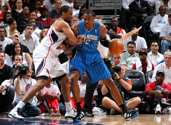ATLANTA, GA - APRIL 22:  Dwight Howard #12 of the Orlando Magic drives into the basket against Jason Collins #34 of the Atlanta Hawks during Game Three of the Eastern Conference Quarterfinals in the 2011 NBA Playoffs at Philips Arena on April 22, 2011 in