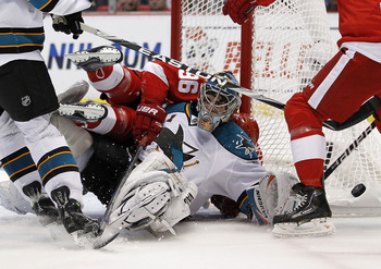 DETROIT - MAY 06:  Thomas Greiss #1 of of the San Jose Sharks tries to keep his eye on the puck after being hit by Tomas Holmstrom #96 of the Detroit Red Wings during Game Four of the Western Conference Semifinals of the 2010 NHL Stanley Cup Playoffs on M