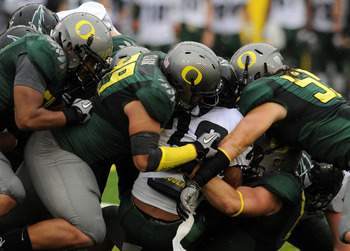 EUGENE, OR - SEPTEMBER 18: Running back Willie Griffin #28 of the Portland State is gang tackled by (L to R) defensive end Kenny Rowe, defensive tackle Zac Clark #99 and linebacker Casey Matthews #55 of the Oregon Ducks in the second quarter of the game a