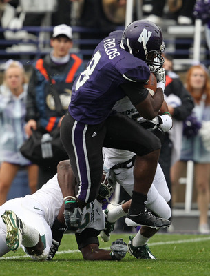 EVANSTON, IL - OCTOBER 23: Demetrius Fields #8 of the Northwestern Wildcats tries to avoid Greg Jones #53 and Johnny Adams #5 of the Michigan State Spartans at Ryan Field on October 23, 2010 in Evanston, Illinois. Michigan State defeated Northwestern 35-2