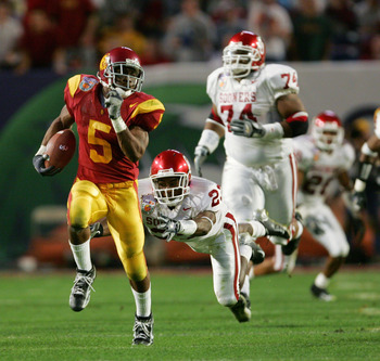MIAMI - JANUARY 4:  Running back Reggie Bush #5 of the USC Trojans runs upfield against safety Brodney Pool #23 and the Oklahoma Sooners in the 2005 FedEx Orange Bowl National Championship on January 4, 2005 at Pro Player Stadium in Miami, Florida.  USC d