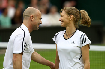 LONDON, ENGLAND - MAY 17:  Andre Agassi (L) and Steffi Graf (R) share a joke during the Mixed Doubles match against Tim Henman and Kim Clijsters  during the 'Centre Court Celebration' at Wimbledon on May 17, 2009 in London, England.  (Photo by Paul Gilham