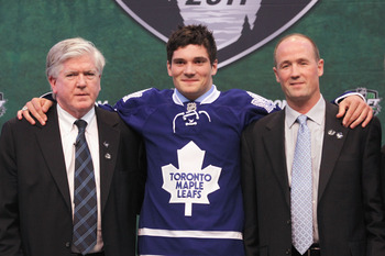 ST PAUL, MN - JUNE 24:  22nd overall pick Tyler Biggs by the Toronto Maple Leafs stands onstage for a photo with President & General Manager Brian Burke (L) and a member of the Toronto Maple Leafs organization during day one of the 2011 NHL Entry Draft at