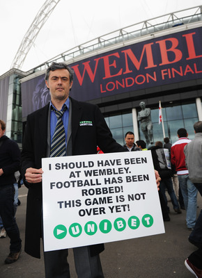 LONDON, ENGLAND - MAY 28:  A Jose Mourinho lookalike holds up a sign outside the stadium ahead of the UEFA Champions League final between FC Barcelona and Manchester United FC at Wembley Stadium on May 28, 2011 in London, England.  (Photo by Michael Regan