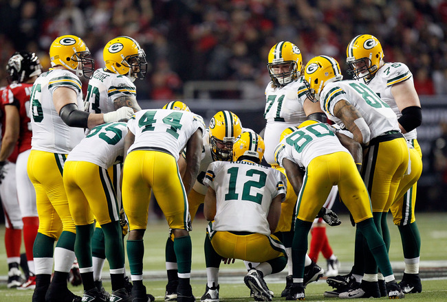 ATLANTA, GA - JANUARY 15:  Quarterback Aaron Rodgers #12 of the Green Bay Packers calls a play in the offensive huddle against the Atlanta Falcons during their 2011 NFC divisional playoff game at Georgia Dome on January 15, 2011 in Atlanta, Georgia. The P