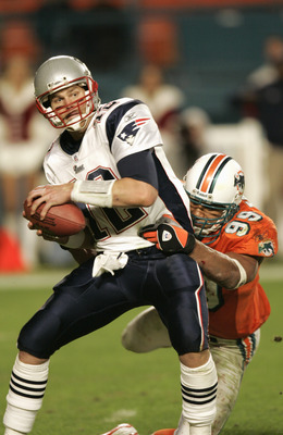 MIAMI - DECEMBER 20:  Jason Taylor #99 of the Miami Dolphins sacks Tom Brady #12 of the New England Patriots during the game at Pro Player Stadium on December 20, 2004 in Miami, Florida. The Dolphins won 29-28.  (Photo by Eliot J. Schechter/Getty Images)