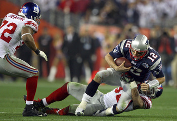 GLENDALE, AZ - FEBRUARY 03:  Quarterback Tom Brady #12 of the New England Patriots is sacked by defensive end Michael Strahan #92 of the New York Giants in the third quarter during Super Bowl XLII on February 3, 2008 at the University of Phoenix Stadium i