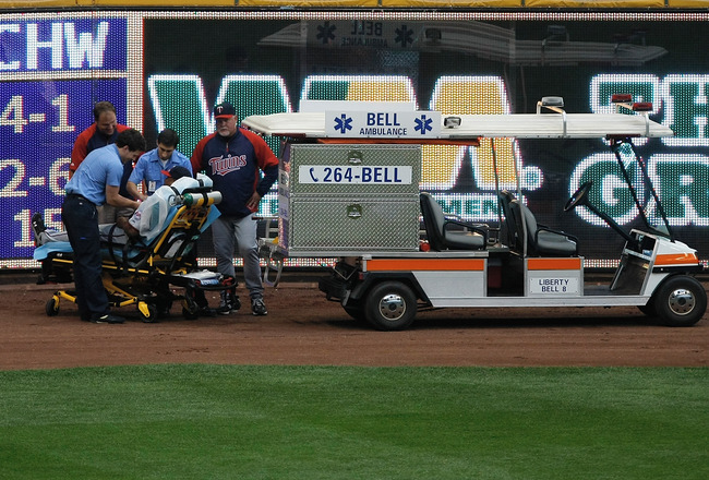 MILWAUKEE, WI - JUNE 25: Delmon Young #21 of the Minnesota Twins is put on a stretcher after running into the left field wall as Ron Gardenhire #35 looks on against the Milwaukee Brewers at the Miller Park on June 25, 2011 in Milwaukee, Wisconsin. (Photo