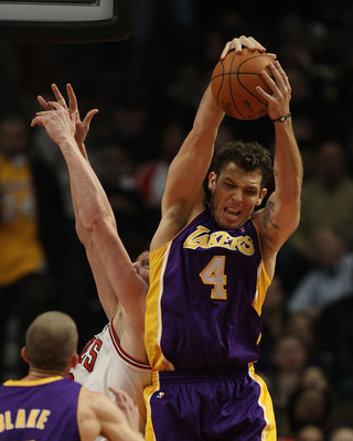 CHICAGO, IL - DECEMBER 10: Luke Walton #4 of the Los Angeles Lakers leaps over Omer Asik #3 of the Chicago Bulls to grab a rebound at the United Center on December 10, 2010 in Chicago, Illinois. NOTE TO USER: User expressly acknowledges and agrees that, b
