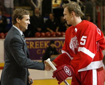 DETROIT - OCTOBER 5:  Nicklas Lidstrom #5 of the Detroit Red Wings skates out on the ice wearing the captain 'C,' as the new captain of the Red Wings, and is greeted by former captain Steve Yzerman prior to facing the Vancouver Canucks during their NHL ga