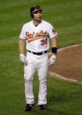 BALTIMORE, MD - JUNE 28: Luke Scott #30 of the Baltimore Orioles walks back to the dugout after striking out swining in the seventh inning against the St. Louis Cardinals at Oriole Park at Camden Yards on June 28, 2011 in Baltimore, Maryland.  (Photo by R