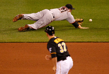 PITTSBURGH - APRIL 26:  Freddy Sanchez #21 of the San Francisco Giants dives for a ball while Lyle Overbay #37 of the Pittsburgh Pirates runs to second base during the game on April 26, 2011 at PNC Park in Pittsburgh, Pennsylvania.  (Photo by Jared Wicker