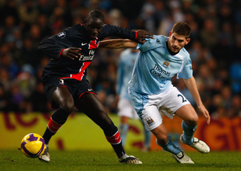 MANCHESTER, UNITED KINGDOM - DECEMBER 03:  Sakho Mamadou of Paris Saint Germain battles for the ball with Ched Evans of Manchester City during the UEFA Cup Group A match between Manchester City and Paris Saint-Germain at The City of Manchester Stadium on
