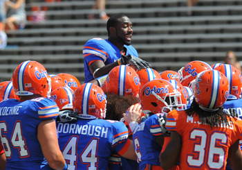 GAINESVILLE, FL - APRIL 9:  Running back Chris Rainey #3 of the Florida Gators climbs to the top of a team huddle before the Orange and Blue spring football game April 9, 2011 at Ben Hill Griffin Stadium in Gainesville, Florida.  (Photo by Al Messerschmid