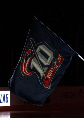 COLUMBUS, OH - MARCH 15:  A member of the Hilliard High School hockey team plants the Columbus Blue Jackets team flag prior to the start of the game against the Boston Bruins on March 15, 2011 at Nationwide Arena in Columbus, Ohio. (Photo by John Grieshop
