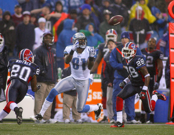 ORCHARD PARK, NY - NOVEMBER 14:  Calvin Johnson #81 of the Detroit Lions catches a pass between Donte Whitner #20 and Leodis McKelvin #28 of the Buffalo Bills at Ralph Wilson Stadium on November 14, 2010 in Orchard Park, New York. The Bills won 14-12.  (P