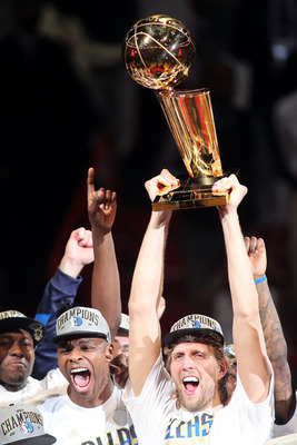 MIAMI, FL - JUNE 12:  Dirk Nowitzki #41 of the Dallas Mavericks holds up the Larry O'Brien trophy as he celebrates with Brendan Haywood #33 and other teammates after the Mavericks won 105-95 in Game Six of the 2011 NBA Finals at American Airlines Arena on