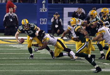 ARLINGTON, TX - FEBRUARY 06: Aaron Rodgers #12 of the Green Bay Packers is sacked by James Harrison #92 of the Pittsburgh Steelers during the second half of Super Bowl XLV at Cowboys Stadium on February 6, 2011 in Arlington, Texas.  (Photo by Streeter Lec