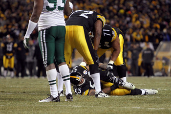 PITTSBURGH, PA - JANUARY 23:  Maurkice Pouncey #53 of the Pittsburgh Steelers grabs his left knee as he lies on the turf against the New York Jets during the 2011 AFC Championship game at Heinz Field on January 23, 2011 in Pittsburgh, Pennsylvania. The St