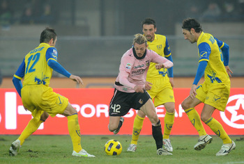VERONA, ITALY - JANUARY 09: Federico Balzaretti (2nd-L) of Palermo compete for the ball with Bostjan Cesar (L), Gennaro Sardo (2nd-R) and Davide Mandelli of Chievo during the Serie A match between AC Chievo Verona and US Citta di Palermo at Stadio Marc'An