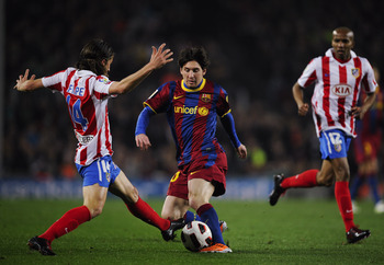 BARCELONA, SPAIN - FEBRUARY 05:  Lionel Messi of Barcelona (L) duels for the ball against Filipe Luis of Atletico Madrid during the La Liga match between Barcelona and Atletico de Madrid at Camp Nou on February 5, 2011 in Barcelona, Spain. Barcelona won 3