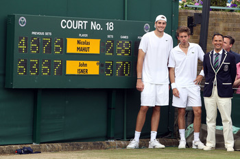 LONDON, ENGLAND - JUNE 24:  John Isner of USA (L) poses after winning on the third day of his first round match against Nicolas Mahut of France (C) with Chair Umpire Mohamed Lahyani on Day Four of the Wimbledon Lawn Tennis Championships at the All England