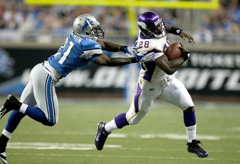DETROIT - SEPTEMBER 20:  Running back Adrian Peterson #28 of the Minnesota Vikings carries the ball past cornerback Phillip Buchanon #31 of the Detroit Lions at Ford Field on September 20, 2009 in Detroit, Michigan. The Vikings won 27-13.  (Photo by Steph