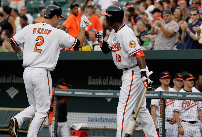 BALTIMORE, MD - JUNE 07: J.J. Hardy #2 of the Baltimore Orioles celebrates his solo home run with teammate Adam Jones #10 during the first inning against the Oakland Athletics at Oriole Park at Camden Yards on June 7, 2011 in Baltimore, Maryland.  (Photo