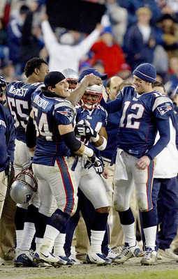 FOXBORO, MA - DECEMBER 27:  Tedy Bruschi #54 and Tom Brady #12 congratulate Ty Law #24 of the New England Patriots after he was taken out of the game against the Buffalo Bills on December 27, 2003 at Gillette Stadium in Foxboro, Massachusetts. The Patriot