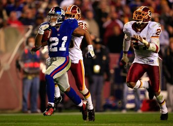 LANDOVER, MD - DECEMBER 30:  Tiki Barber #21 of the New York Giants runs the ball for his third touchdown against Kenny Wright #25 of the Washington Redskins at FedEx Field on December 30, 2006 in Landover, Maryland.  (Photo by Jamie Squire/Getty Images)