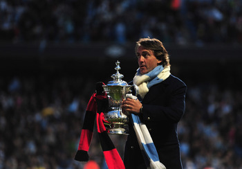 MANCHESTER, ENGLAND - MAY 23:  Roberto Mancini manager of Manchester City lifts the FA Cup to the fans during the Manchester City FA Cup Winners Parade at the City of Manchester stadium on May 23, 2011 in Manchester, United Kingdom.  (Photo by Jamie McDon