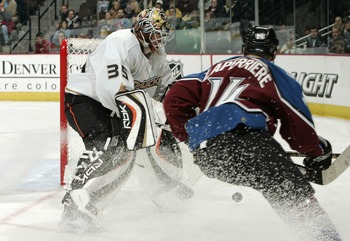 DENVER - FEBRUARY 13:  Goalie Jean-Sebastien Giguere #35 of the Anaheim Ducks clears the puck from behind the goal just ahead of Ian Laperriere #14 of the Colorado Avalanche in third period NHL action February 13, 2006 at the Pepsi Center in Denver, Color
