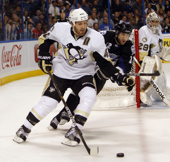 TAMPA, FL - APRIL 25: Brooks Orpik #44 of the Pittsburgh Penguins skates with the puck against Simon Gagne #12 of the Tampa Bay Lightning in Game Six of the Eastern Conference Quarterfinals during the 2011 NHL Stanley Cup Playoffs at the St. Pete Times Fo