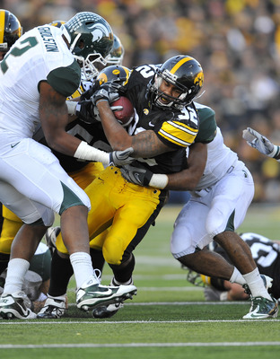 IOWA CITY, IA - OCTOBER 30-  Running back Adam Robinson #32 of the University of Iowa Hawkeyes is tackled by linebacker William Gholston #2 of the Michigan State Spartans during the second half of play at Kinnick Stadium on October 30, 2010 in Iowa City,