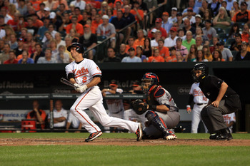 BALTIMORE, MD - JUNE 29:  J.J. Hardy #2 of the Baltimore Orioles follows his hit against catcher Yadier Molina #4 of the St. Louis Cardinals looks on at Oriole Park at Camden Yards on June 29, 2011 in Baltimore, Maryland.  (Photo by Rob Carr/Getty Images)