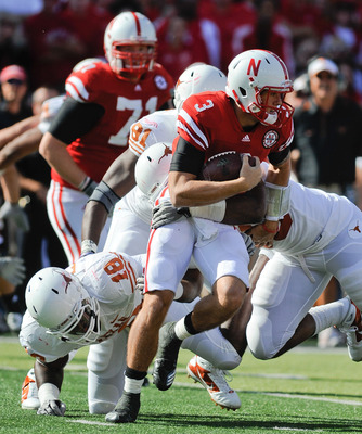 LINCOLN, NE - OCTOBER 16: Quarterback Taylor Martinez #3 of the Nebraska Cornhuskers runs from the grasp of Texas Longhorns linebacker Emmanuel Acho #18 during first half action of their game at Memorial Stadium on October 16, 2010 in Lincoln, Nebraska. T