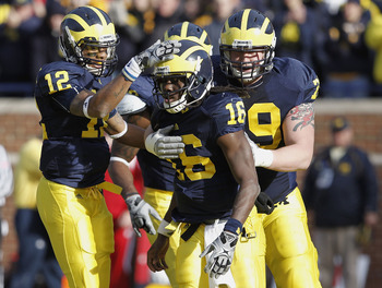 ANN ARBOR, MI - NOVEMBER 20:  Denard Robinson #16 of the Michigan Wolverines is congratulated by Roy Roundtree #12 and Perry Dorrenstein #79 after a third quarter touchdown against the Wisconsin Badgers at Michigan Stadium on November 20, 2010 in Ann Arbo