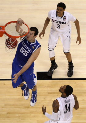 HOUSTON, TX - APRIL 02:  Josh Harrellson #55 of the Kentucky Wildcats dunks the ball Jeremy Lamb #3  and Alex Oriakhi #34 of the Connecticut Huskies during the National Semifinal game of the 2011 NCAA Division I Men's Basketball Championship at Reliant St