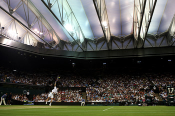 WIMBLEDON, ENGLAND - JUNE 29:  Andy Murray of Great Britain serves under the new Centre Court roof during the men's singles fourth round match against Stanislas Wawrinka of Switzerland on Day Seven of the Wimbledon Lawn Tennis Championships at the All Eng