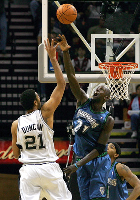 SAN ANTONIO - DECEMBER 23:  Forward Kevin Garnett #21 of the Minnesota Timberwolves blocks a shot against Tim Duncan #21 of the San Antonio Spurs on December 23, 2004 at the SBC Center in San Antonio, Texas.  NOTE TO USER:  User expressly acknowledges and