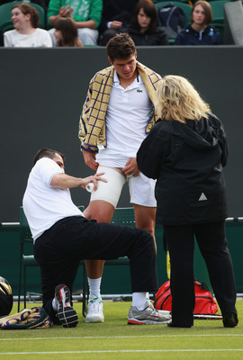 LONDON, ENGLAND - JUNE 22:  Milos Raonic of Canada seeks medical assistance after falling down during his second round match against Gilles Muller of Luxembourg on Day Three of the Wimbledon Lawn Tennis Championships at the All England Lawn Tennis and Cro
