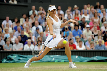 LONDON, ENGLAND - JUNE 28:  Maria Sharapova of Russia returns a shot during her quarterfinal round match against Dominika Cibulkova of Slovakia on Day Eight of the Wimbledon Lawn Tennis Championships at the All England Lawn Tennis and Croquet Club on June