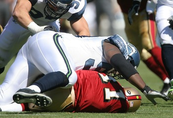 SAN FRANCISCO - SEPTEMBER 30:  Quarterback Alex Smith #11 of the San Francisco 49ers lays injured with a separated shoulder under defensive lineman Rocky Bernard #99 during a game at Monster Park September 30, 2007 in San Francisco, California.  (Photo by