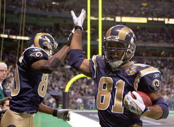 ST. LOUIS - DECEMBER 5: Torry Holt #81 of the St. Louis Rams celebrates his touchdown with teammate Isaac Bruce #80 in the first half against the San Francisco 49ers on December 5, 2004 at the Edward Jones Dome in St. Louis, Missouri. The St. Louis Rams d