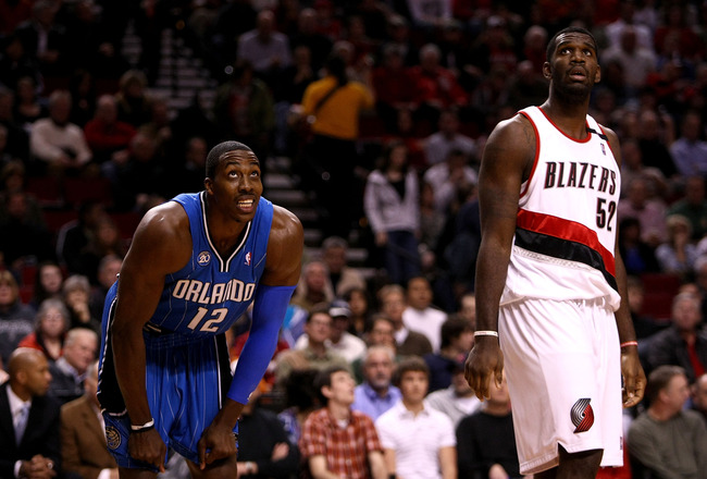 PORTLAND, OR - DECEMBER 09:  Dwight Howard #12 of the Orlando Magic watches a freethrow with Greg Oden #52 of the Portland Trail Blazers for a rebound at the Rose Garden on December 9, 2008 in Portland, Oregon.  NOTE TO USER: User expressly acknowledges a