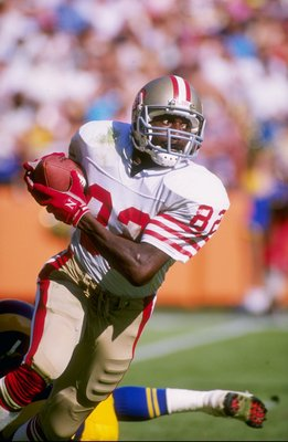 Wide receiver John Taylor of the San Francisco 49ers runs down the field during a game against the Los Angeles Rams at Anaheim Stadium in Anaheim, California.