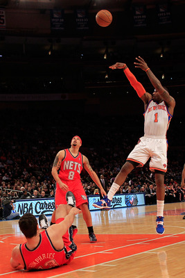 NEW YORK, NY - MARCH 30:  Amar'e Stoudemire #1 of the New York Knicks shoots over Deron Williams #8 and Kris Humphries #43 of the New Jersey Nets at Madison Square Garden on March 30, 2011 in New York City. NOTE TO USER: User expressly acknowledges and ag