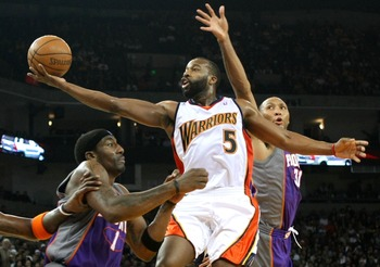 OAKLAND, CA - NOVEMBER 26:  Baron Davis #5 of the Golden State Warriors shoots over Shawn Marion #31 and Amare Stoudemire #1 of the Phoenix Suns on November 26, 2007 at Oracle Arena in Oakland, California. NOTE TO USER: User expressly acknowledges and agr