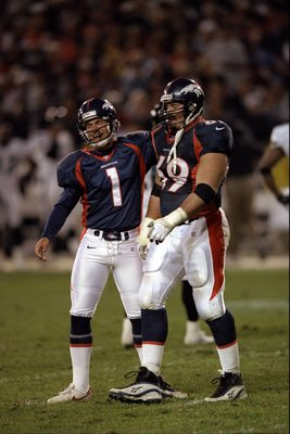 25 Oct 1998: Kicker Jason Elam #1 of the Denver Broncos walks with teammate Mark Schlereth #69 during a game against the Jacksonville Jaguars at Mile High Stadium in Denver, Colorado. The Broncos defeated the Jaguars 37- 24.