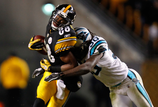 PITTSBURGH - DECEMBER 23:  Emmanuel Sanders #88 of the Pittsburgh Steelers is hit by Charles Godfrey #30 of the Carolina Panthers after catching a pass during the game on December 23, 2010 at Heinz Field in Pittsburgh, Pennsylvania.  (Photo by Jared Wicke